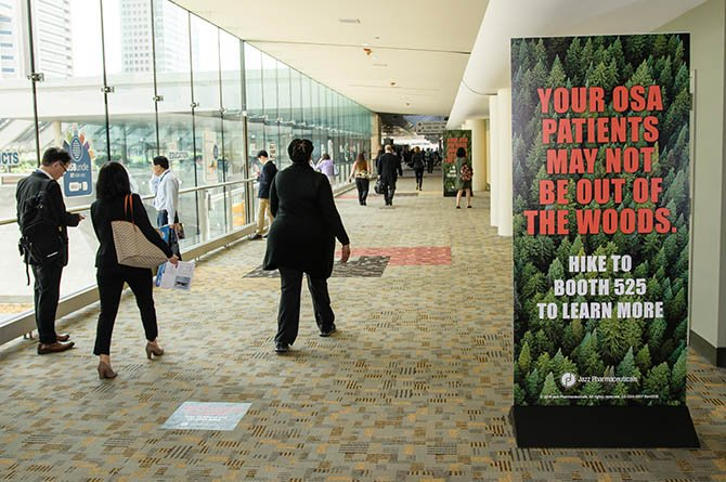 convention hallway showing people walking past a large freestanding sign with sponsored content